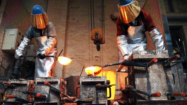 Zwei Giesser bei ihrer Arbeit mit flüssigem Metall.
