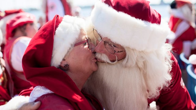 Ein als Samichläuse verkleidetes Paar küsst sich.