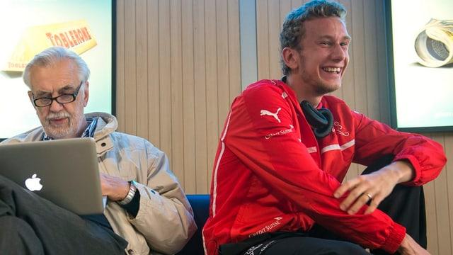 Fabian Lustenberger sitzt am Flughafen neben einem Passanten mit Laptop.