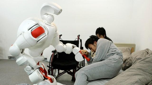 Ein grosser weisser Roboter unterstützt einen jüngeren Mann, der sich in ein Bett legt.