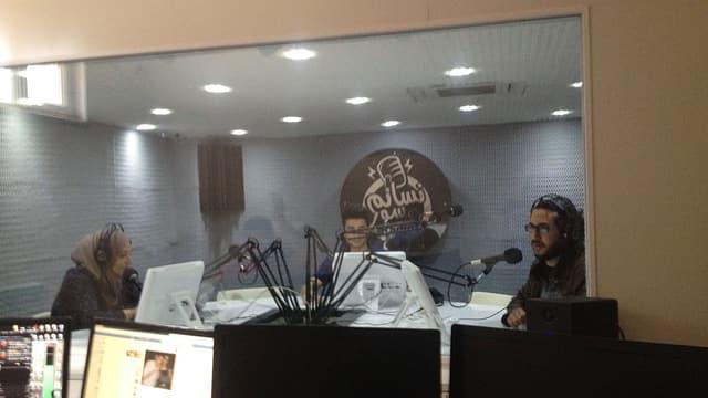 Hinter einer Scheibe sitzen zwei Männer und eine Frau am Mikrofon, sie tragen Kopfhörer.