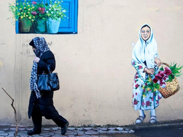 Frau läuft an Mauer vorbei, auf die eine lachende Frau mit Blumenkorb gezeichnet ist.