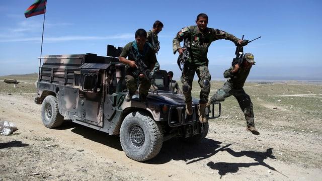 Afghanische Soldaten springen von einem Geländewagen.
