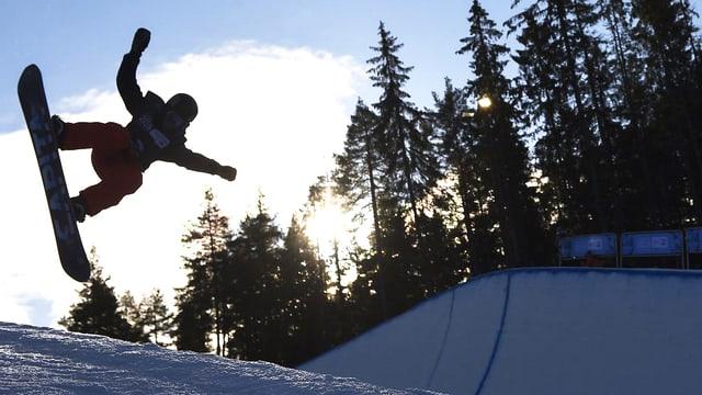Snowboarder springt in der Halfpipe.