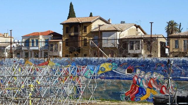 Bemalte Grenzmauer, im Hintergrund Häuser