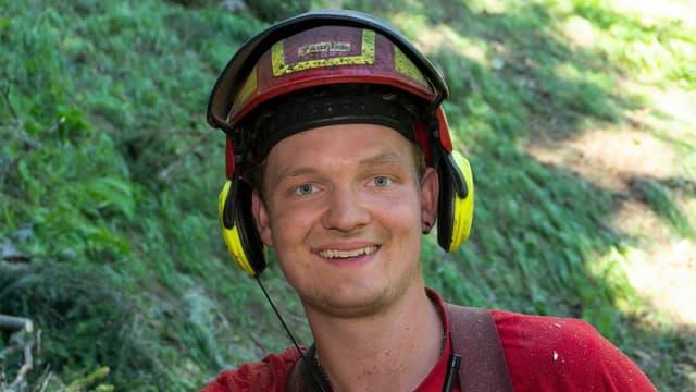 Junger Mann mit Helm im Wald