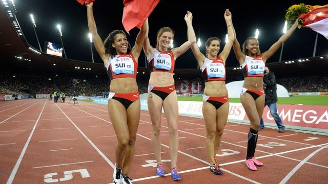 Die Schweizer Frauen-Staffel jubelt mit Schweizer Flaggen und Blumenstrauss.
