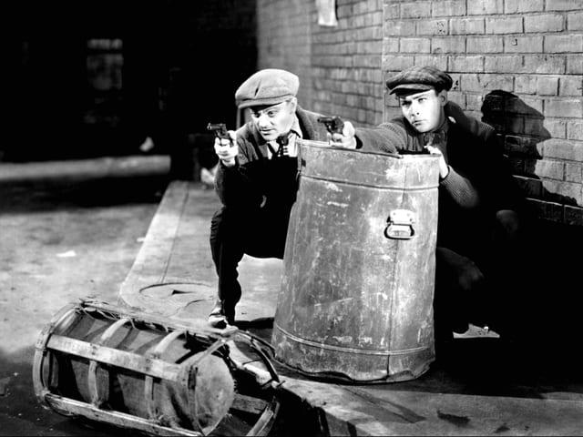 Cagney und ein Mann verstecken sich hinter einer Mülltonne und zielen mit Pistolen.