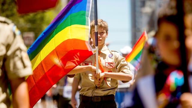Ein amerikanischer Pfadfinder mit Uniform hält eine Regenbogenfahne