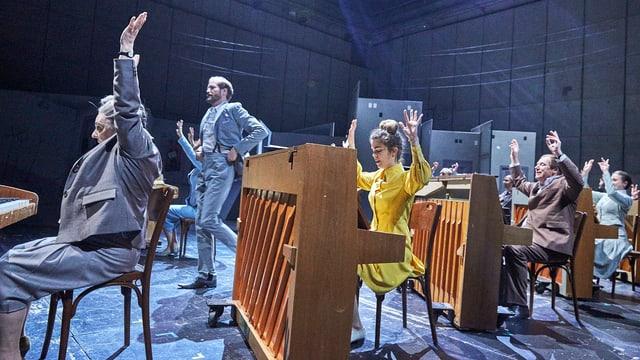 Szene aus einem Theaterstück: Vier Pianisten sitzen hintereinander und halten die Hände ein die Luft.