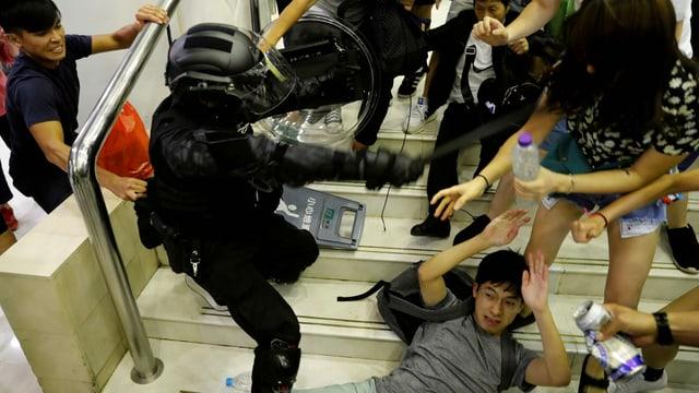 Ein Polizist in Vollmontur schlägt auf Demonstranten ein,