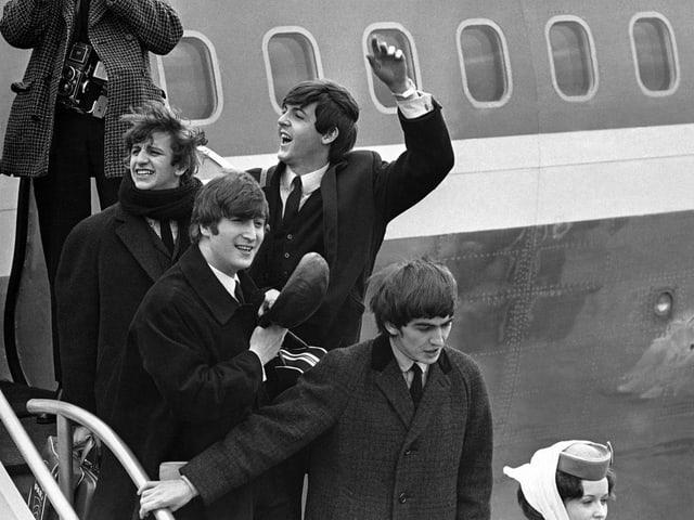 Die vier jungen Mitglieder der Beatles steigen aus dem Flugzeug, einer winkt.