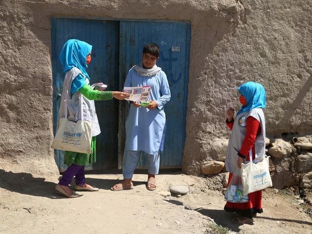 Zwei Frauen bringen einem Mann vor seiner Haustüre Informationsbroschüren. Die Frauen tragen ein hellblaues Kopftuch, was die Farbe von UNICEF symbolisiert.