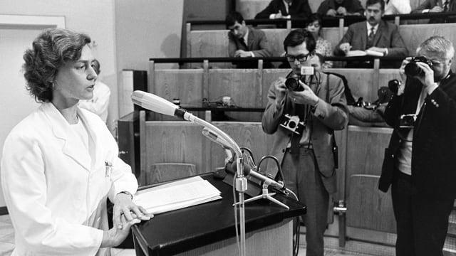 Schwarzweiss-Foto: Frau in weissem Kittel steht am Rednerpult im Hörsaal. Zwei Männer machen Fotos.