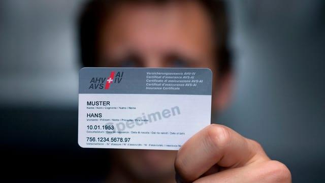 Ein Mann streckt eine AHV-Karte in die Kamera.