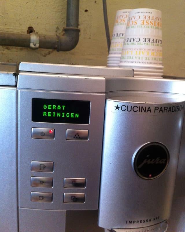 """Eine Kaffemaschine. Die Anzeige leuchtet mit dem Schriftzug """"Gerät reinigen""""."""