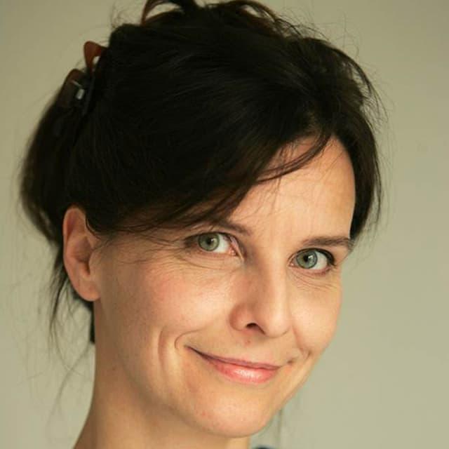 Porträt einer lächlenden Frau mit hochtesteckten Haaren.