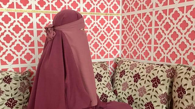 Nikabträgerin mit rosarotem Gewand vor gemusterter Wand
