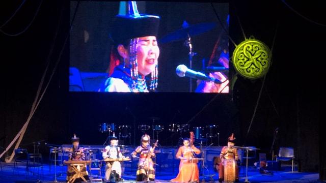 Fünf Musiker demonstrieren ihre Künste auf einer grossen Bühne mit einem Bildschirm im Hintergrund.