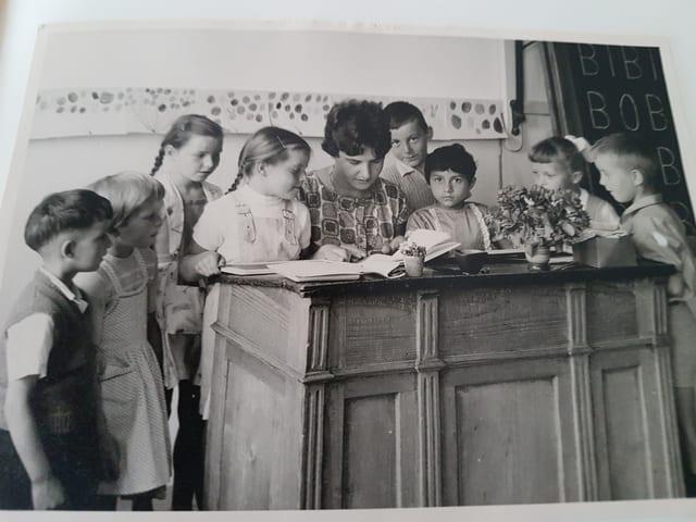Lehrerin betrachtet Buch am Pult umringt von Kindern.