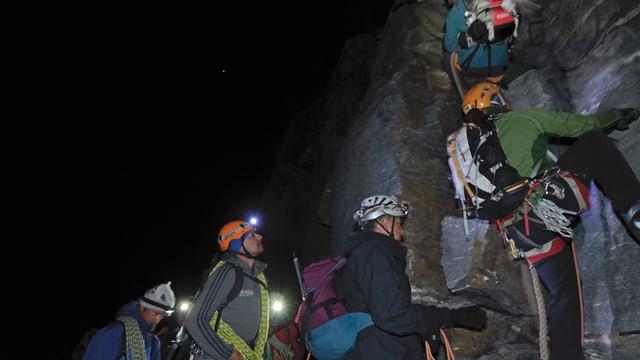 Bergsteiger im nächtlichen Dunkel stehen Schlange vor einer Steilwand.
