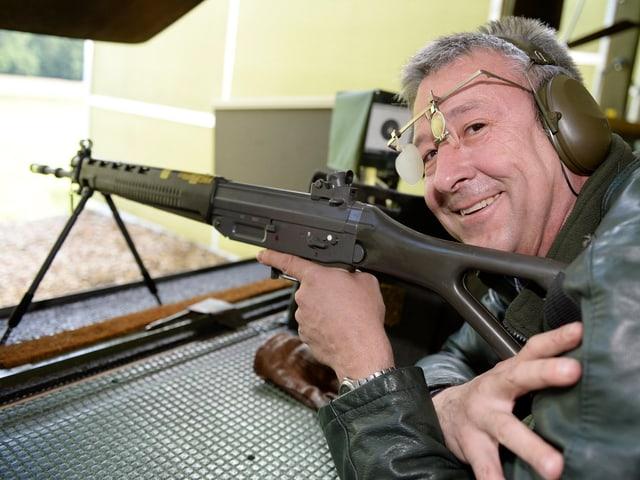 Ein Mann liegt auf dem Bauch, ein Sturmgewehr im Ansatz, und lächelt in die Kamera.