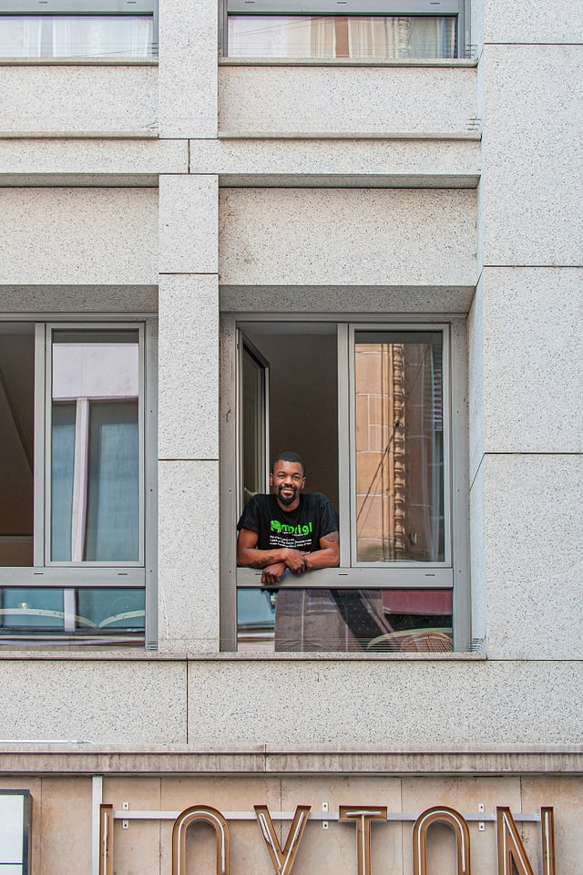 Ein junger Mann lehnt aus einem Fenster, darunter ein Leuchtschriftzug.