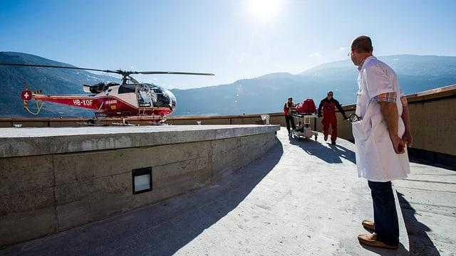 Ein Arzt wartet auf den Antransport eines Verletzten, im Hintergrund ein Helikopter.