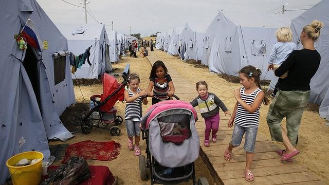 Kinder und Frauen in einem Zeltlager.