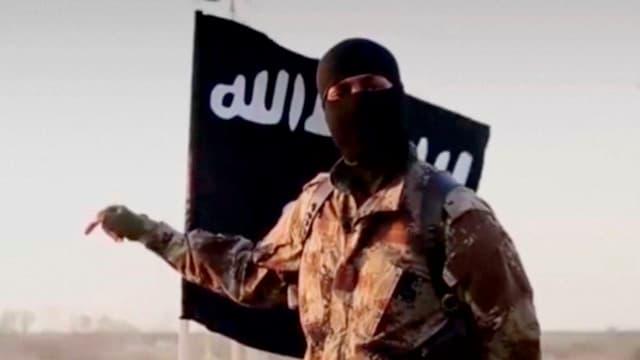 Ein maskierter Mann steht in einem Tarnanzug vor einer schwarzen IS-Flagge, Aussenaufnahme.