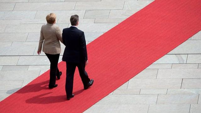 Merkel und Cameron schreiten auf dem roten Teppich.