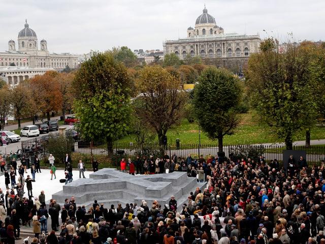 Mehrere hundert Menschen stehen um das Denkmal, das wie ein liegendes X aussieht und begehbar ist.