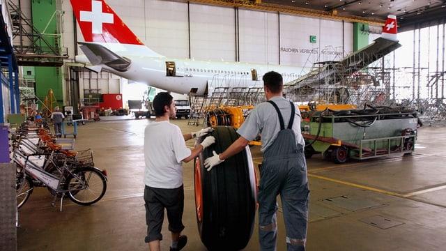 Zwei Mitarbeiter rollen einen fast manhshohen Flugzeugreifen zu einem im Hintergrund in der Halle stehenden Flugzeug mit dem Schweizerkreuz an der Heckflosse.
