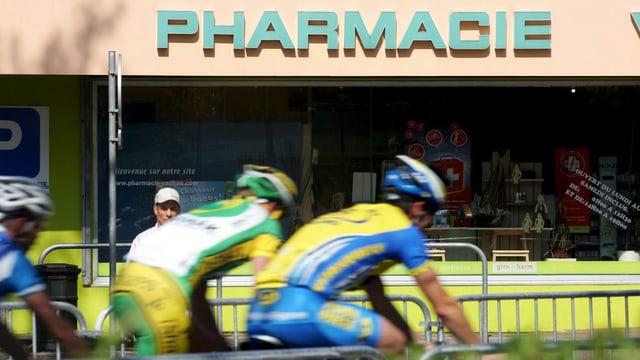 Zwei Radrennfahrer fahren an einer Apotheke vorbei.