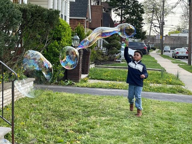 Ein Knabe spielt mit riesigen Seifenblasen in einer Strasse in Newark.