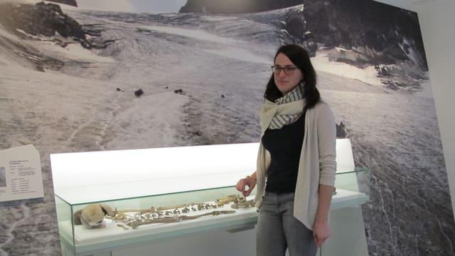 Projektleiterin Leandra Reitmeier vor einer Glasvitrine mit Funden aus dem Gletscher.