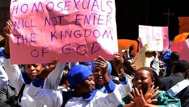 """Frauen halten ein Transparent hoch mit der Aufschrift: """"Homosexuals will not enter the kingdom of God""""."""