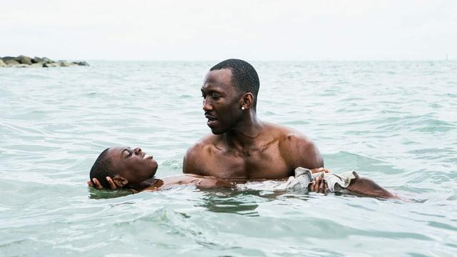 Filmszene: Ein Mann steht im Meer und hält einen Jungen über Wasser.