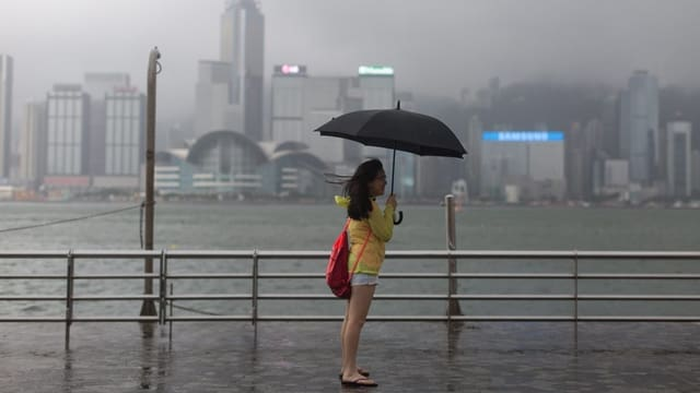 Ina dunna cun in parisol nair stat davant ina saiv - davostiers vesan ins la citad da Hongkong ch'è tut turbla pervi dal taifun.
