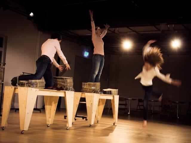 Drei Frauen auf einer Theaterbühne. Zwei davon knien und stehen auf Holztischen.