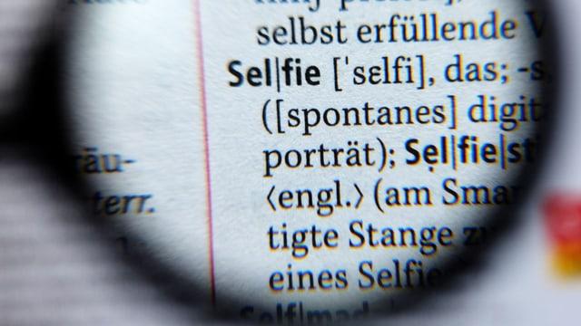 Eine Lupe vor einer Duden-Seite. Erkennbar ist das Wort Selfie.
