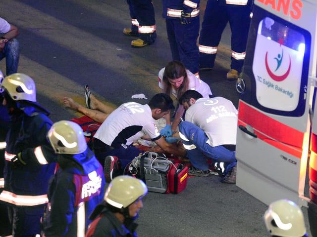 Sanitäter verarzten verletzte Person.
