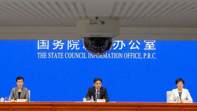 Medienkonferenz mit drei Personen vor blauem Hintergrund.