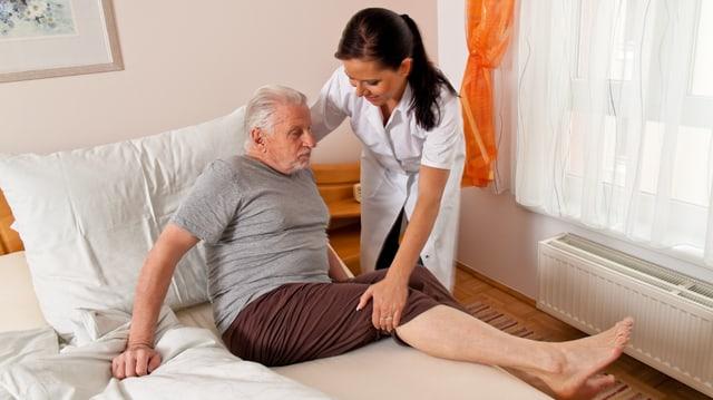 Krankenpflegerin hilft älterem Mann aus dem Bett