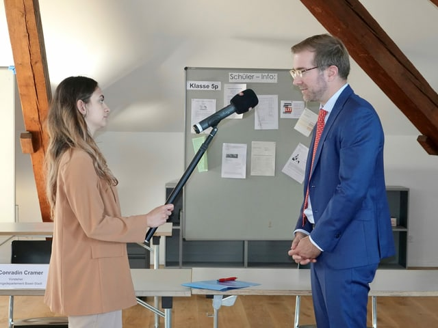 Eine Radiojournalistin interviewt den Basler Erziehungsdirektor Conradin Cramer.