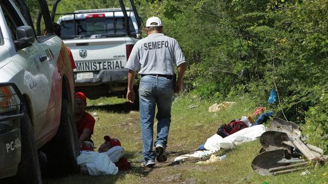 Ein Forensiker geht neben einem Wagen, am Boden liegen Kleidungsstücke