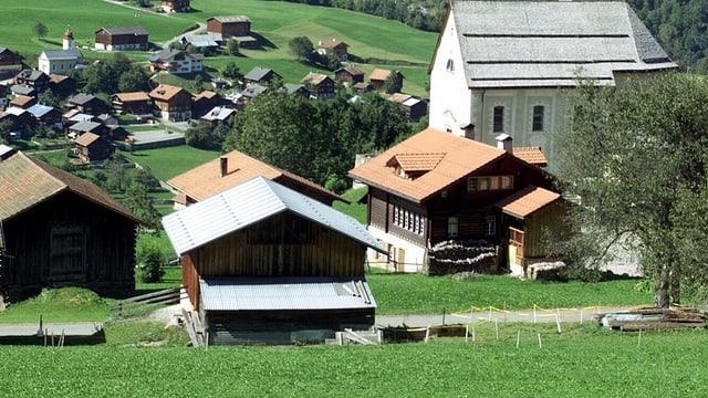 Häuser, Ställe, und eine Kirche, davor grüne Wiese