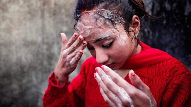 Eine junge Frau wäscht mit Seifenschaum ihre Stirn.