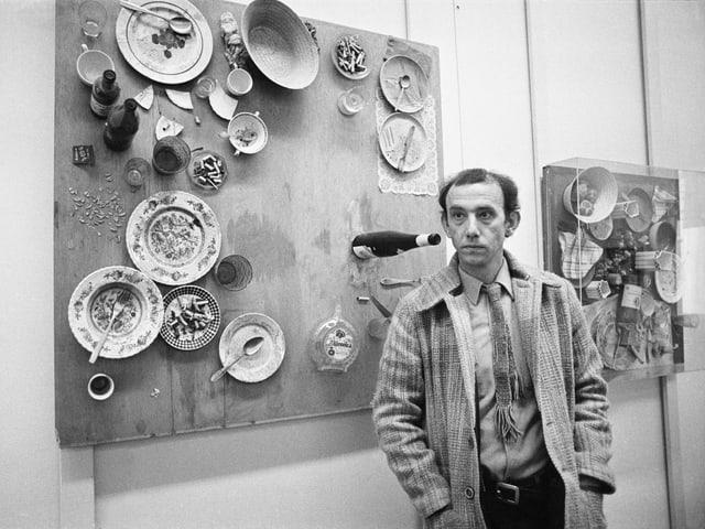 Ein Mann steht vor zwei Tischplatten, die vertikal an der Wand hängen.