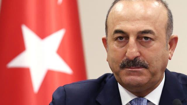 Mann vor türkischer Flagge.